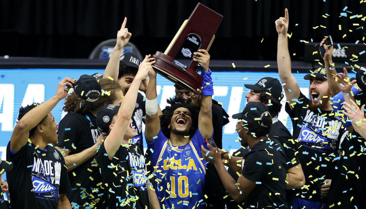 INDIANAPOLIS, INDIANA - MARCH 30: Tyger Campbell #10 of the UCLA Bruins celebrates with the East Regional Champion trophy after defeating the Michigan Wolverines 51-49 in the Elite Eight round game of the 2021 NCAA Men's Basketball Tournament at Lucas Oil Stadium on March 30, 2021 in Indianapolis, Indiana. (Photo by Andy Lyons/Getty Images)