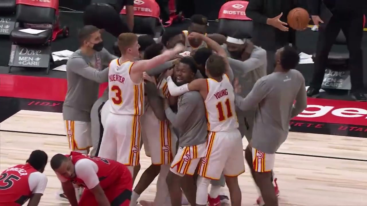 The Atlanta Hawks celebrate after a buzzer beater. They're all in a pile. Two Raptors players are in the foreground, dejected.