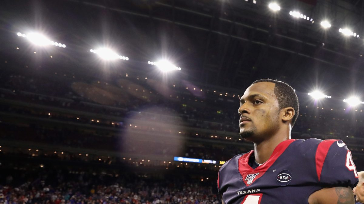 Quarterback Deshaun Watson #4 of the Houston Texans walks off the field following the AFC Wild Card Playoff game against the Buffalo Bills at NRG Stadium on January 04, 2020 in Houston, Texas. Watson is dressed in his uniform. In the background are stadium lights and fans.