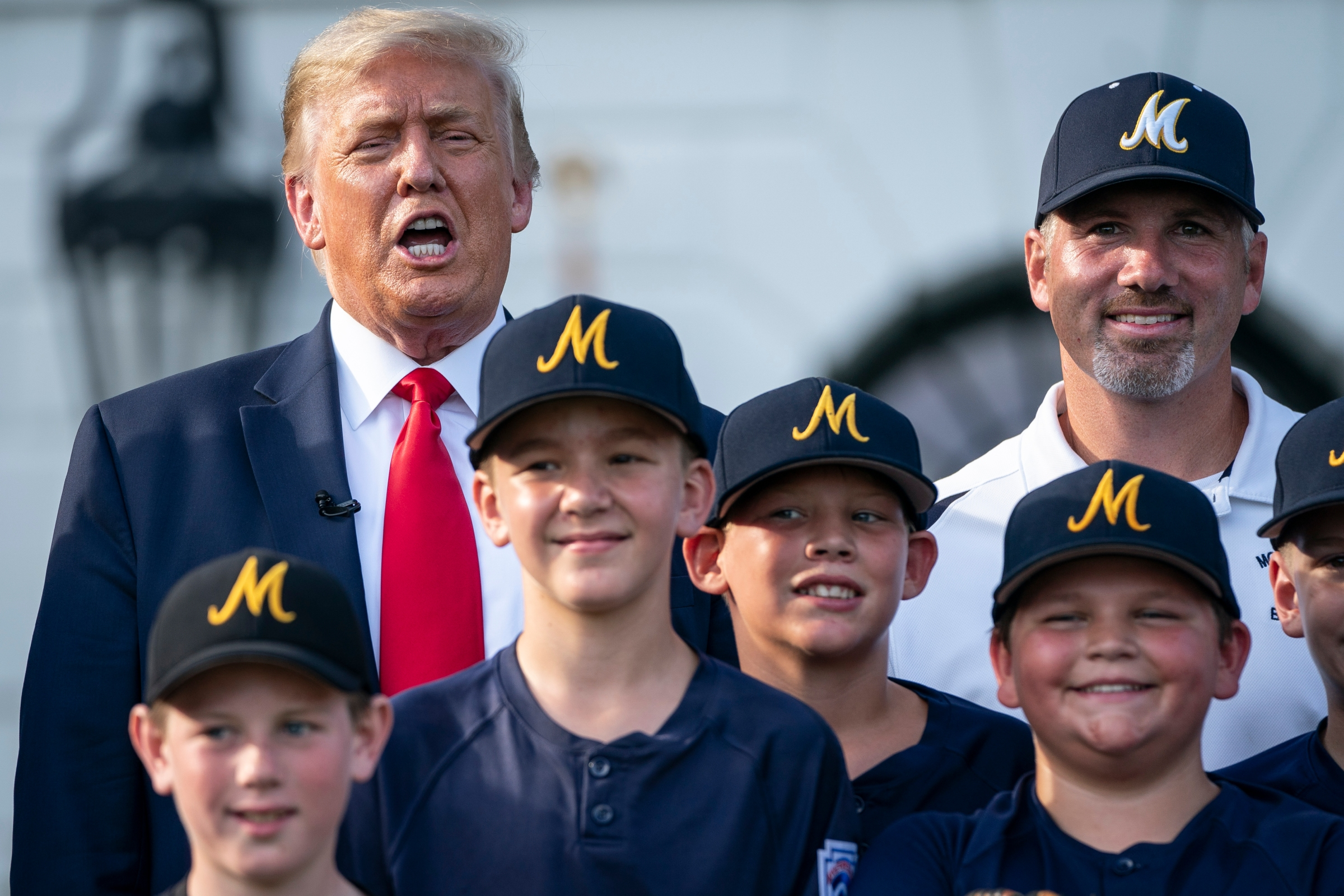 Donald Trump yelling something while posing for a photo with some Little League kids, in 2020.