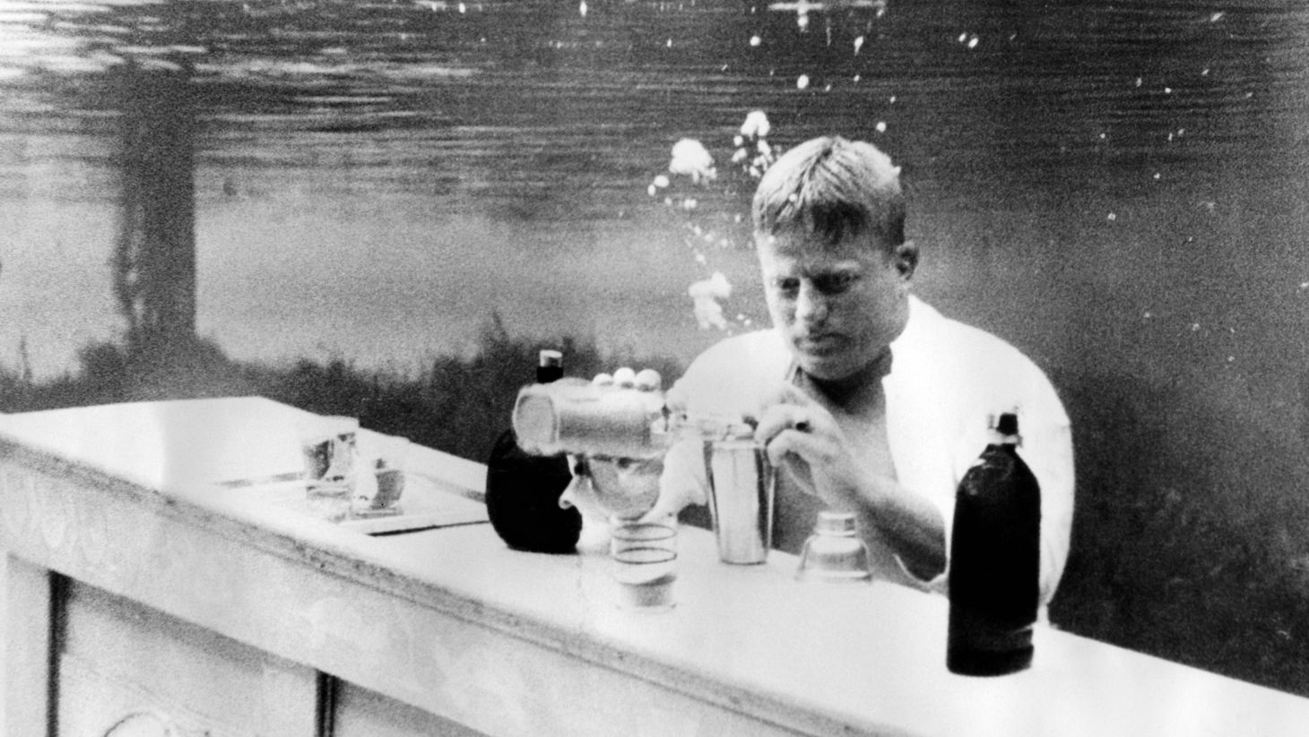 Picture taken on January 15, 1937 at Palm Springs showing a bartender mixing a cocktail under water in a swimming pool. (Photo by - / ACME / AFP) (Photo by -/ACME/AFP via Getty Images)