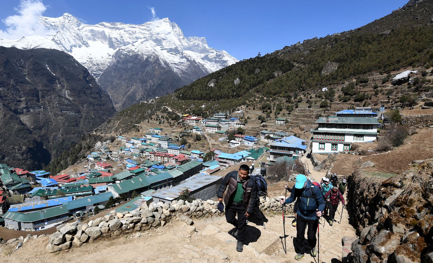 Trekkers walk along a path at Namche Bazar town in the Everest region of Solukhumbu district on April 25, 2021. (Photo by PRAKASH MATHEMA / AFP) (Photo by PRAKASH MATHEMA/AFP via Getty Images)