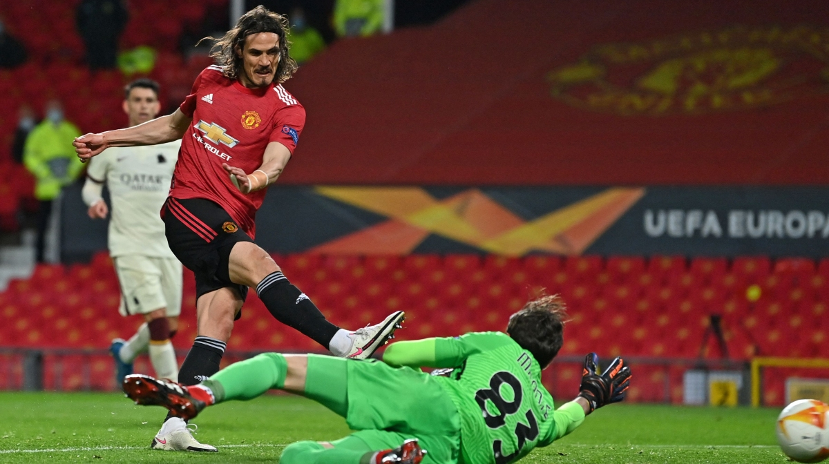Manchester United's Uruguayan striker Edinson Cavani (L) shoots past Roma's Italian goalkeeper Antonio Mirante to score their third goal during the UEFA Europa League semi-final, first leg football match between Manchester United and Roma at Old Trafford stadium in Manchester, north west England, on April 29, 2021.