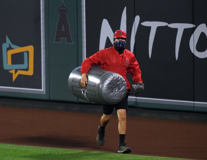 A stadium worker removes a large inflatable trash can prop from the field.