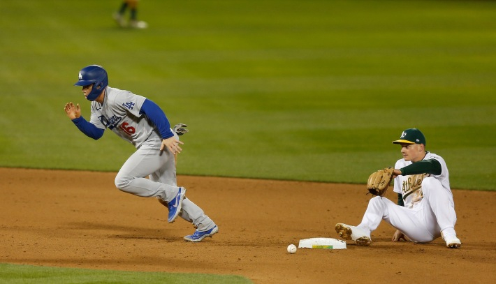 OAKLAND, CALIFORNIA - APRIL 05: Will Smith #16 of the Los Angeles Dodgers runs to third base after colliding with Matt Chapman #26 of the Oakland Athletics in the top of the eighth inning at RingCentral Coliseum on April 05, 2021 in Oakland, California. (Photo by Lachlan Cunningham/Getty Images)