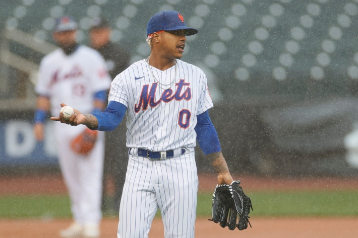 Marcus Stroman of the Mets stands on the mound while it rains.