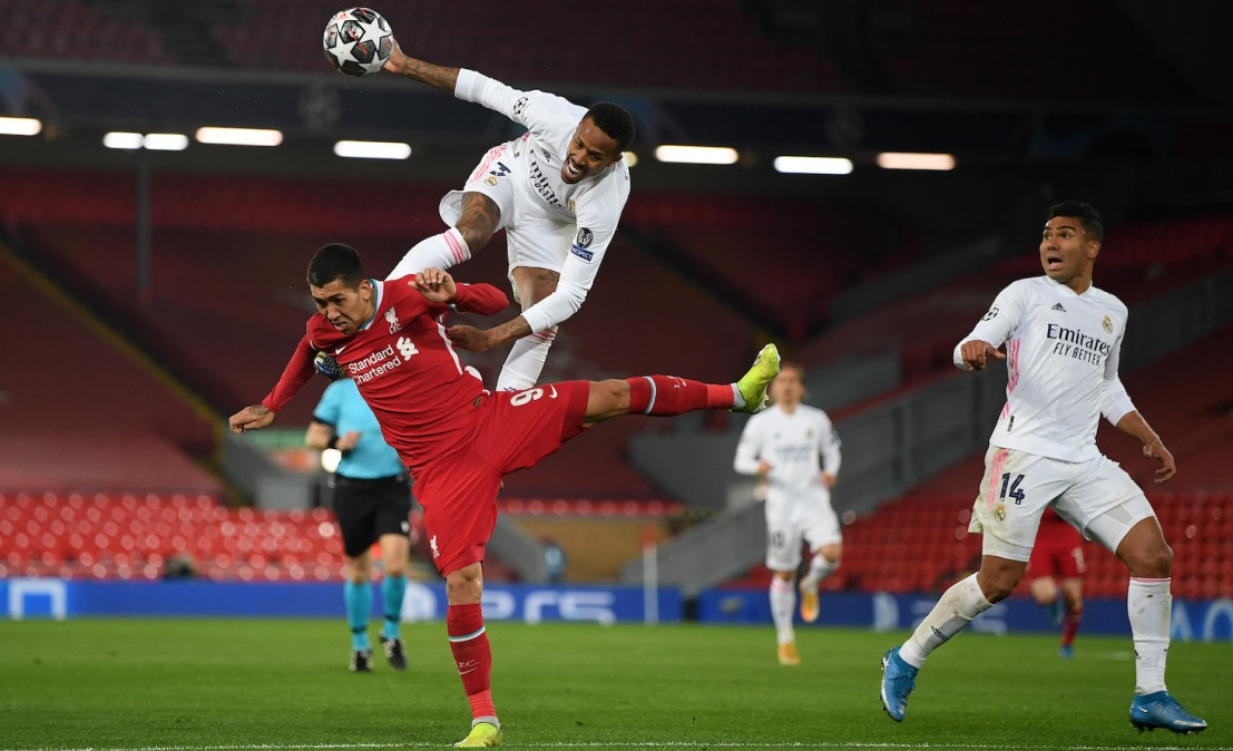 Roberto Firmino of Liverpool battles for possession with Eder Militao of Real Madrid during the UEFA Champions League Quarter Final Second Leg match between Liverpool FC and Real Madrid at Anfield on April 14, 2021 in Liverpool, England.
