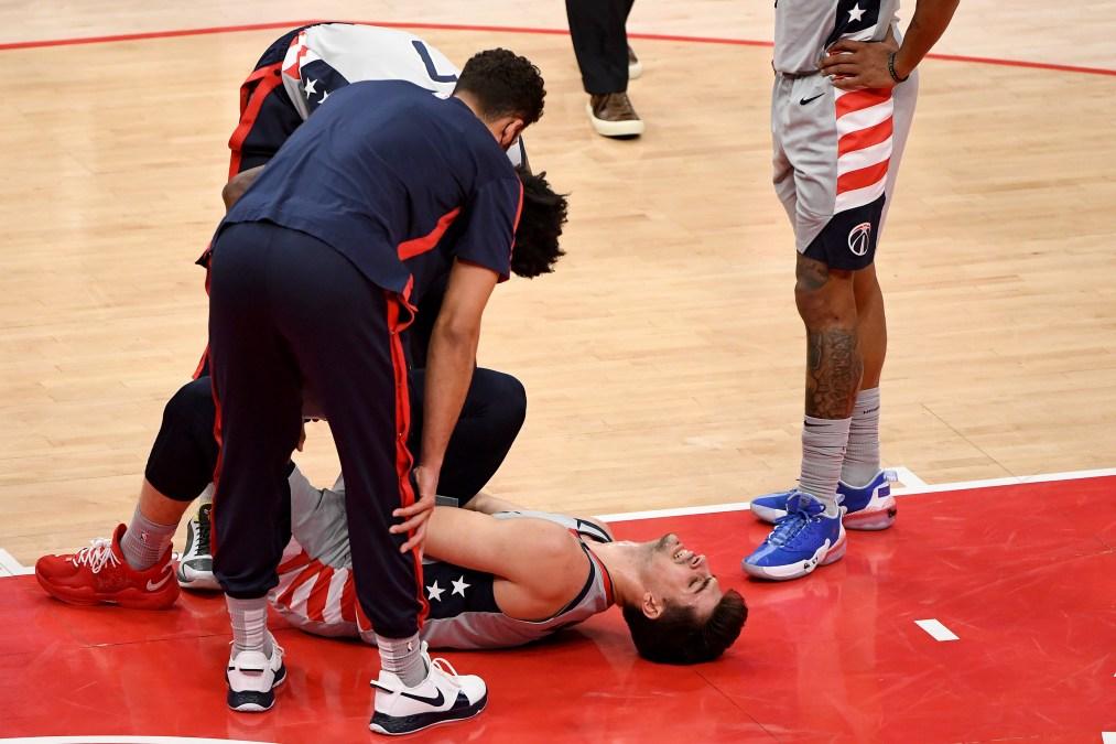 Wizards rookie Deni Avdija lies injured on the court.