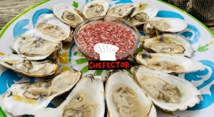 A plate of oysters, a bowl of mignonette sauce, and the Chefector badge