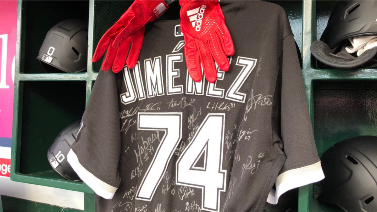 A jersey of Eloy Jimenez, with his batting gloves, signed by his teammates and hung in the dugout during Thursday's season-opener.
