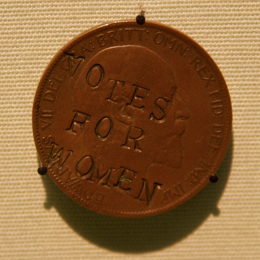 """A suffragette-defaced penny is stamped with """"VOTES FOR WOMEN."""""""