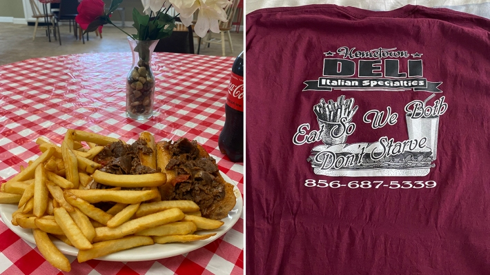 "A split image: A cheesesteak surrounded by fries on a table with a flower and a soda; and a t-shirt that says ""HOMETOWN DELI: Eat So We Both Don't Starve"""