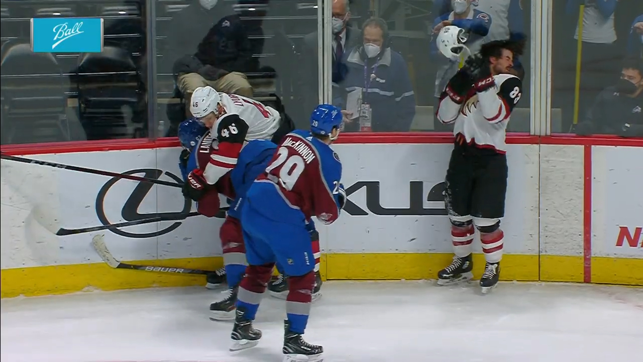 Nathan MacKinnon tosses Conor Garland's helmet back at his chest.
