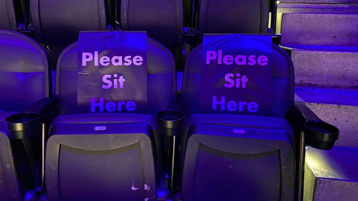 Two seats in an arena at an NBA game. They are black. There are steps next to them. Both seats have a cover on them that says 'PLEASE SIT HERE'