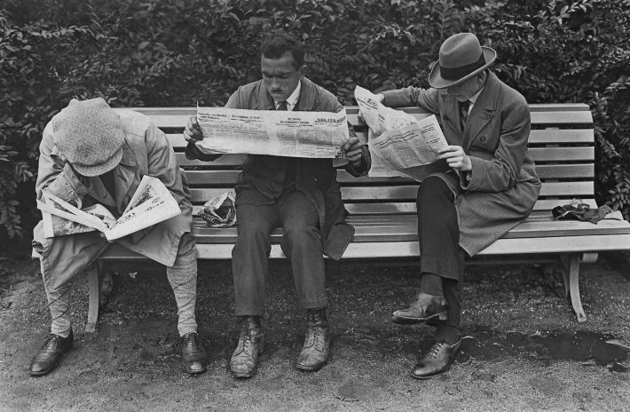 Three men sitting on a park bench reading the newspaper