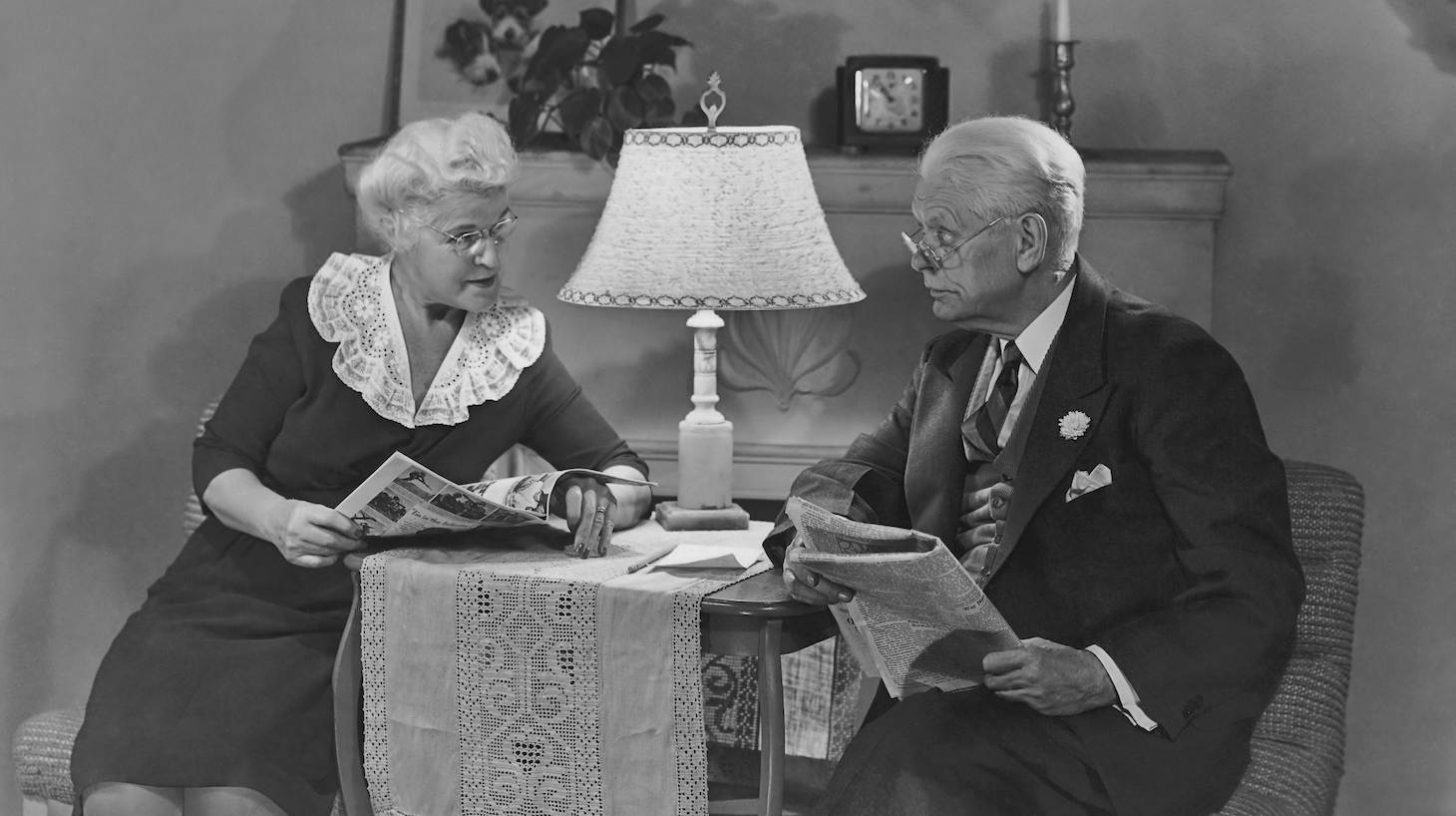 An old man reads a newspaper as his wife looks through a magazine circa 1940's. (Photo by FPG/Getty Images)