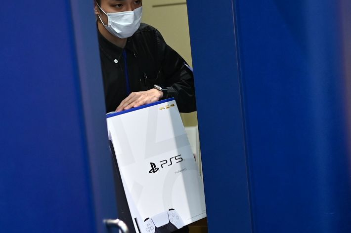 An employee rolls out the new Sony PS5 in Japan.