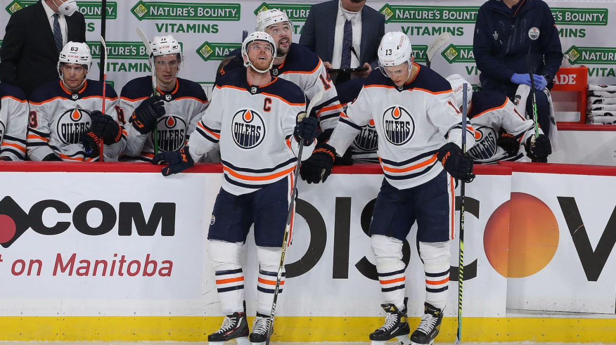 WINNIPEG, MANITOBA - MAY 23: Connor McDavid #97 and Jesse Puljujarvi #13 of the Edmonton Oilers react after the Jets tied up Game Three of the First Round of the 2021 Stanley Cup Playoffs against the Winnipeg Jets on May 23, 2021 at Bell MTS Place in Winnipeg, Manitoba, Canada. (Photo by Jason Halstead/Getty Images)