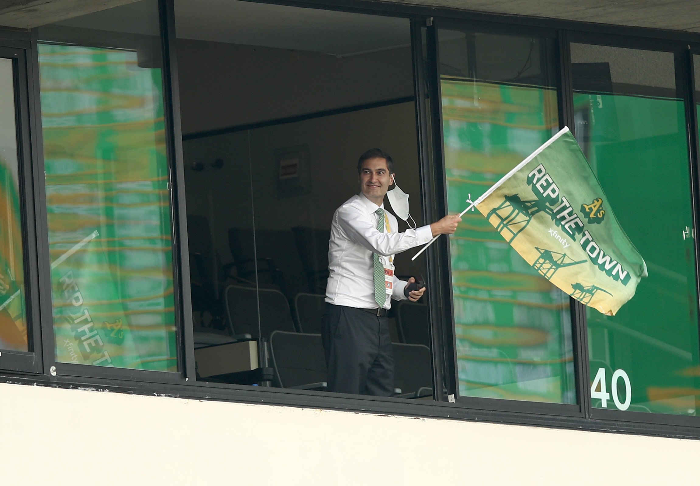 Oakland Athletics team president Dave Kaval waving his team's flag during the 2020 playoffs.