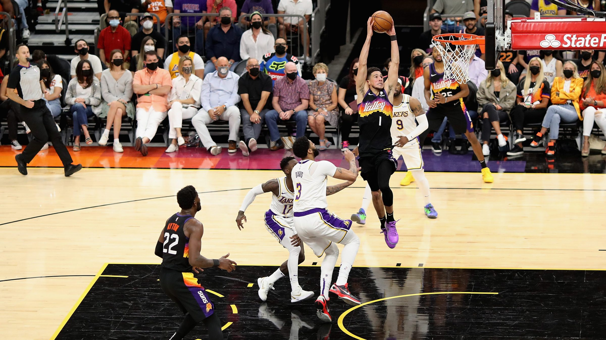 Devin Booker #1 of the Phoenix Suns slam dunks the ball past Anthony Davis #3 of the Los Angeles Lakers during the first half of Game One of the Western Conference first-round playoff series at Phoenix Suns Arena on May 23, 2021 in Phoenix, Arizona. The Suns defeated the Lakers 99-90.