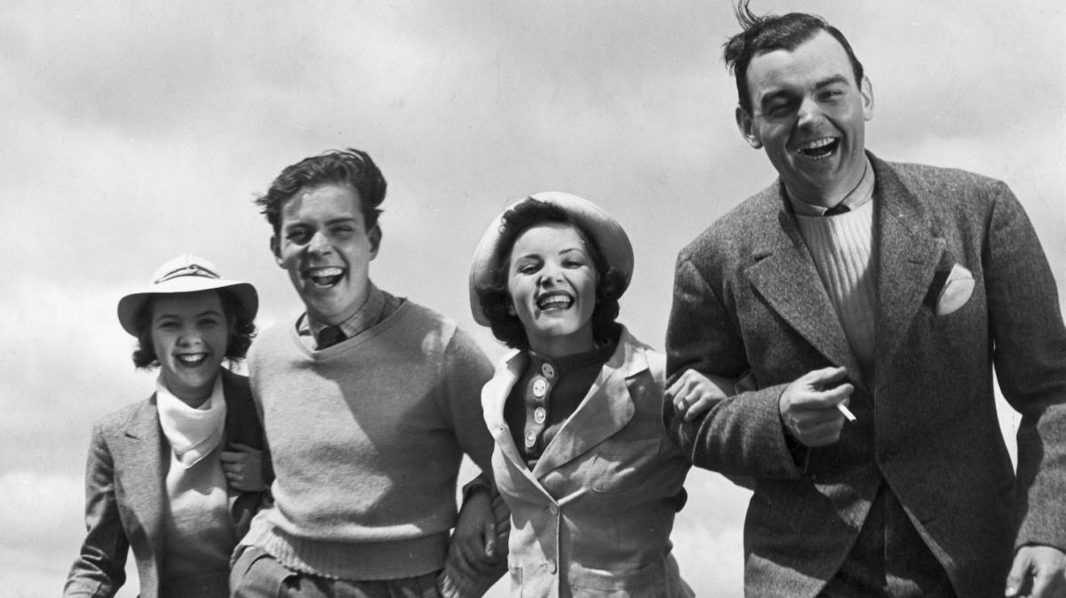circa 1945: Two couples walk arm-in-arm outdoors, laughing. The wind blows the ladies' hats and the men's hair. (Photo by Hulton Archive/Getty Images)