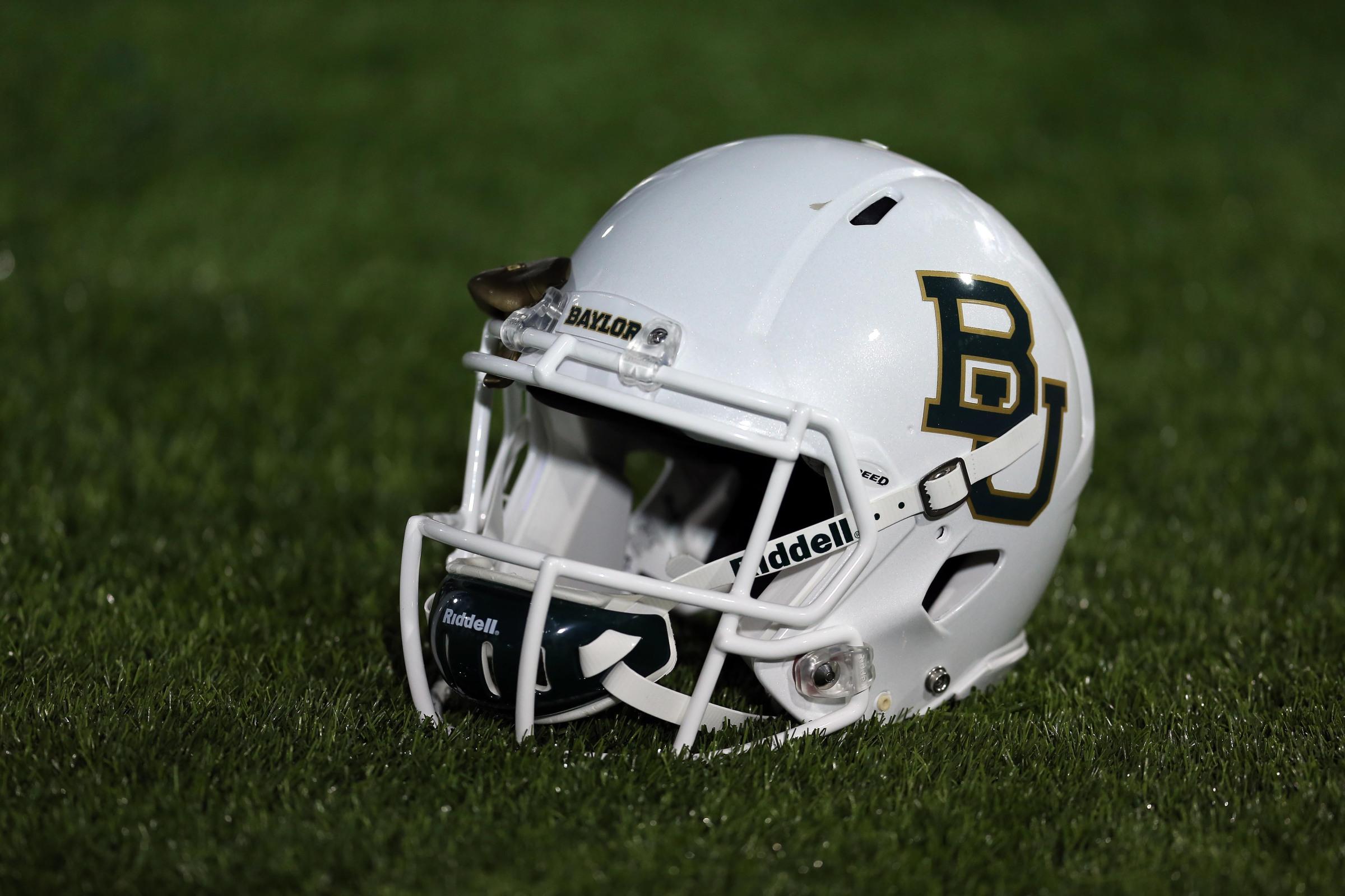 a baylor bears football helmet sits on some grass