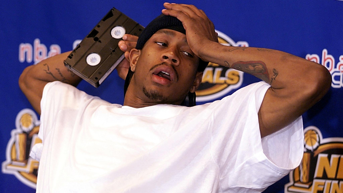 Allen Iverson at a press conference, holding a VHS cassette tape