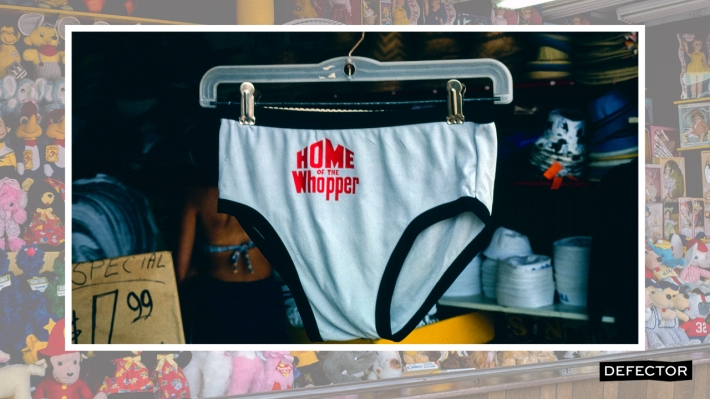 """A pair of speedo swim trunks that say """"HOME OF THE WHOPPER"""" on them"""