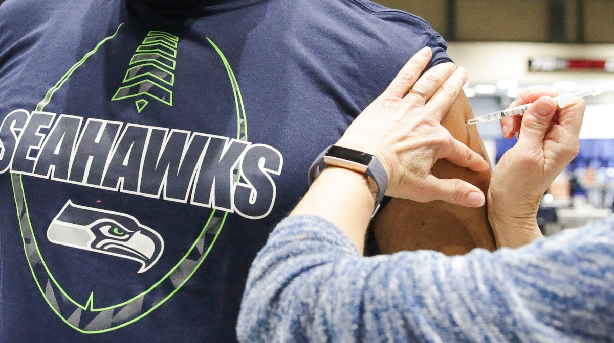 Cleveland Hughes wears Seahawks gear as he gets the Pfizer Covid-19 vaccine from Andrea Barnett during opening day of the Community Vaccination Site, a collaboration between the City of Seattle, First & Goal Inc., and Swedish Health Services at the Lumen Field Event Center in Seattle, Washington on March 13, 2021. (Photo by Jason Redmond / AFP) (Photo by JASON REDMOND/AFP via Getty Images)