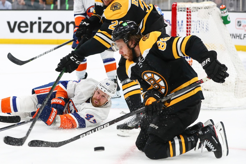 Leo Komarov and David Pastrnak fight for the puck