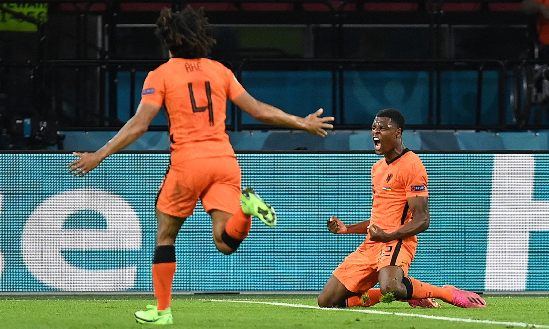 Netherlands' defender Denzel Dumfries (R) celebrates after scoring the third goal during the UEFA EURO 2020 Group C football match between the Netherlands and Ukraine at the Johan Cruyff Arena in Amsterdam on June 13, 2021.