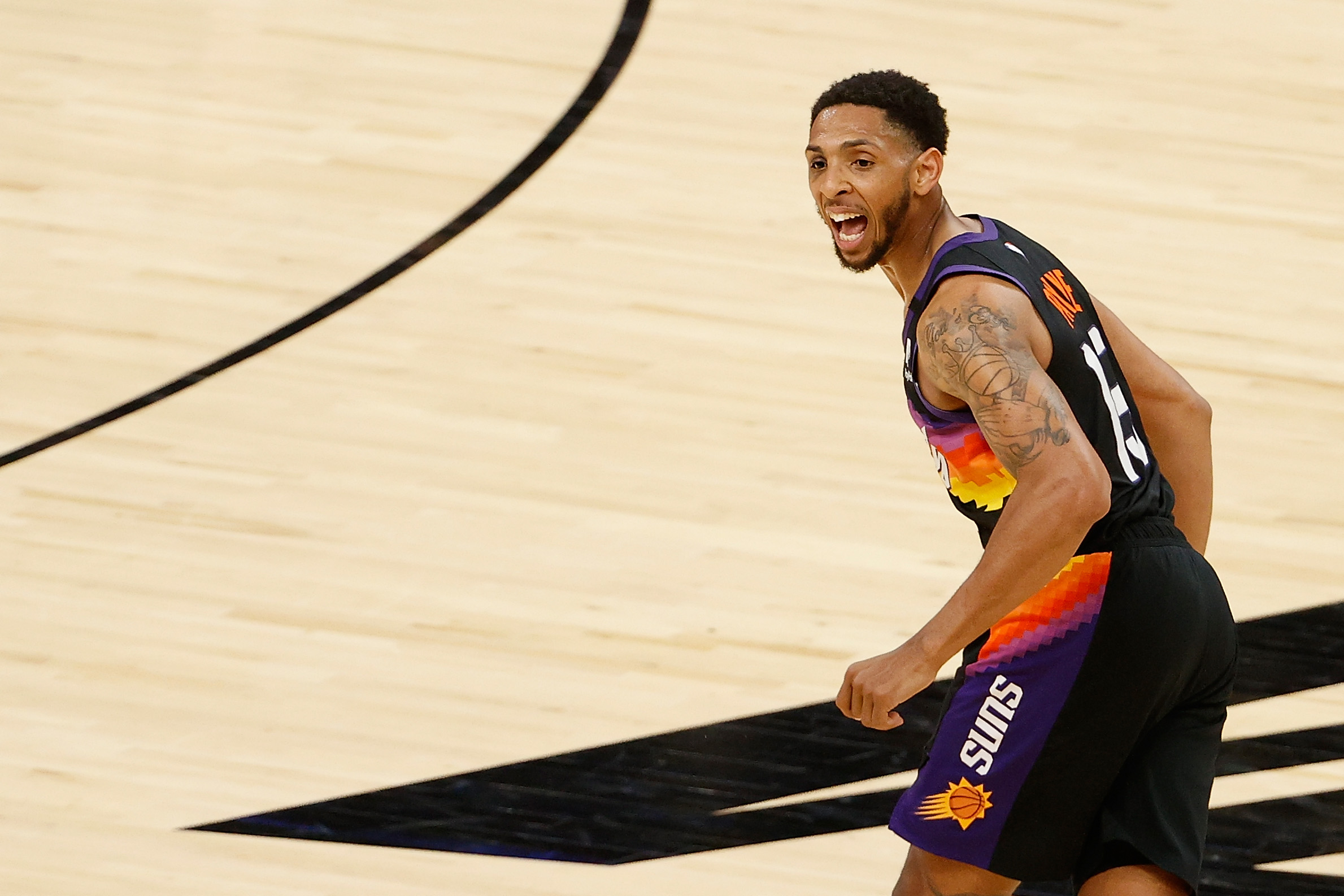 Cameron Payne in a Suns jersey, looking happy.
