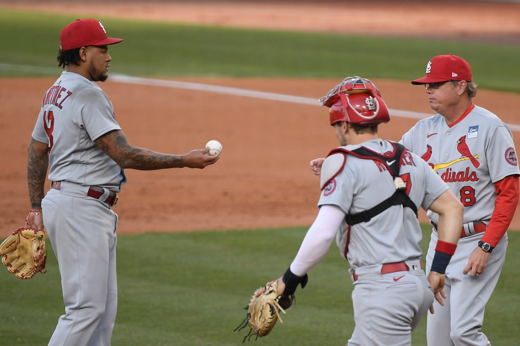 A shell-shocked Carlos Martinez hands the ball to manager Mike Shildt after registering just two outs.