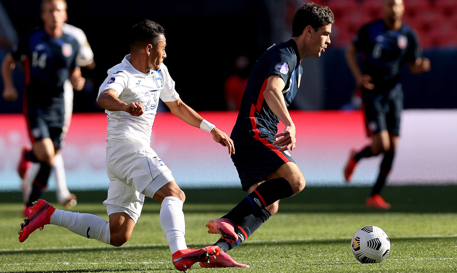 Gio Reyna #7 of USA advances the ball against Diego Rodriguez #23 of Honduras in the first half during Game 1 of the Semifinals of the CONCACAF Nations League Finals of at Empower Field At Mile High on June 03, 2021 in Denver, Colorado.