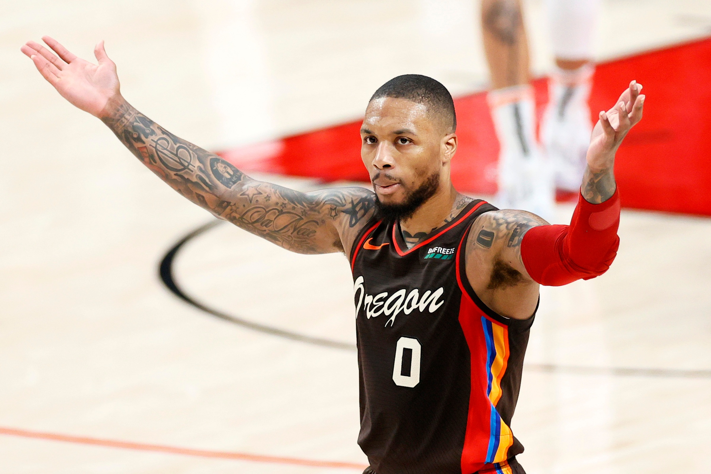 Damian Lillard gestures to the crowd during a playoff game.