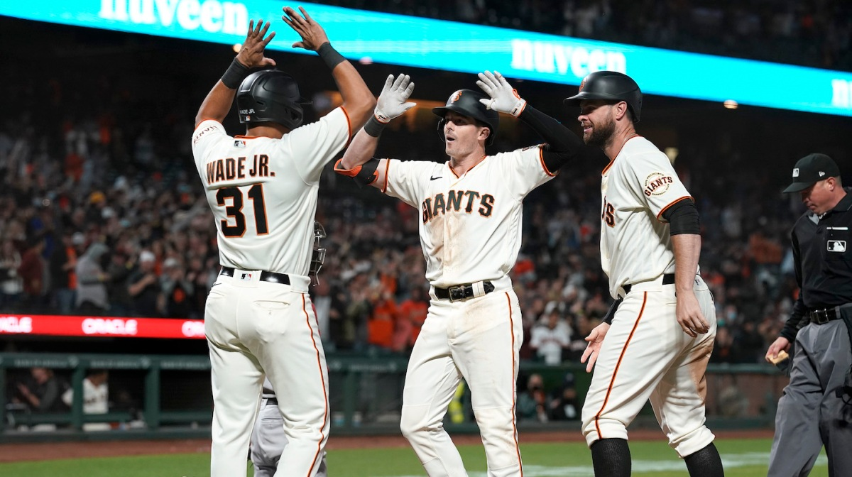 SAN FRANCISCO, CALIFORNIA - JUNE 15: Mike Yastrzemski #5, LaMonte Wade Jr #31 and Brandon Belt #9 of the San Francisco Giants celebrates after Yastrzemski hit a grand slam home run to put the Giants ahead of the Arizona Diamondbacks 9-8 in the bottom of the eighth inning at Oracle Park on June 15, 2021 in San Francisco, California. The Giants won the game 9-8. (Photo by Thearon W. Henderson/Getty Images)