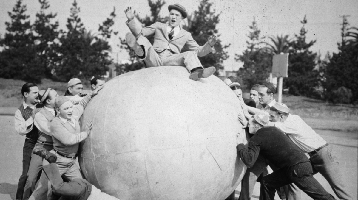 Two groups of men push on opposite sides of a large ball, on top of which sits a man who is losing his balance in a still from the silent film, 'Going Great'. (Photo by Hulton Archive/Getty Images)
