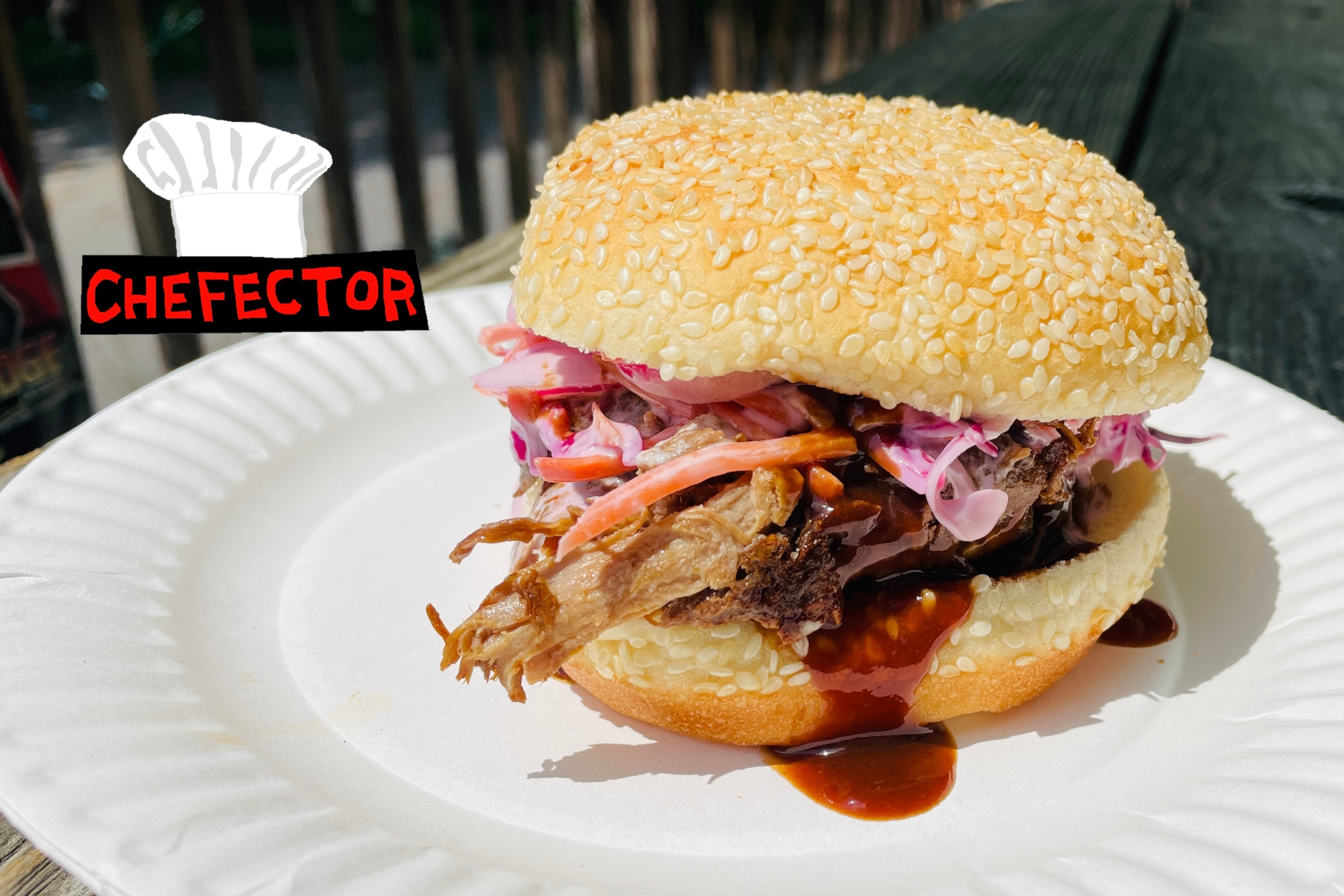 A pulled pork sandwich on a paper plate.