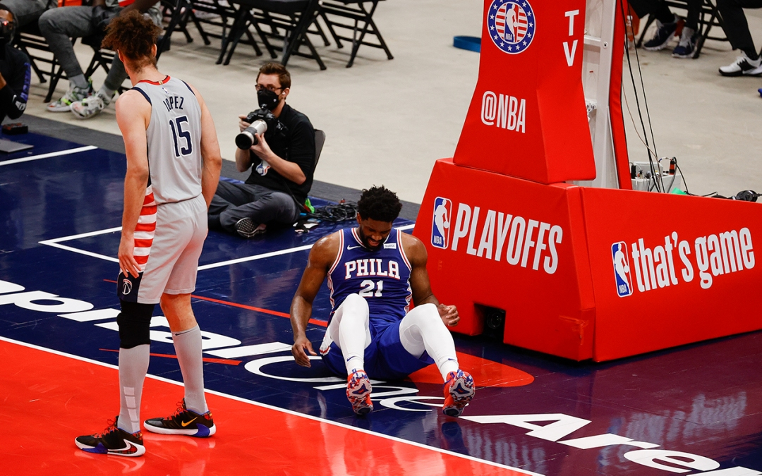 Joel Embiid lies on the court, clearly injured. Robin Lopez looks back at him.