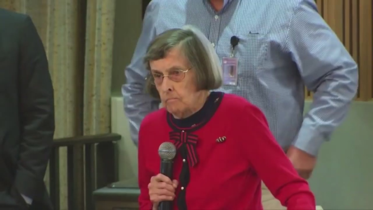 A photo of Greta Rogers as she spoke at a Phoenix City Council meeting in 2018. She is wearing a red sweater and holding a microphone. She also is wearing glasses. She has silver hair, cut short.