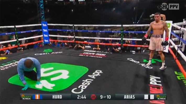 The ref wipes up a wet dollar sign logo in the center of the ring.