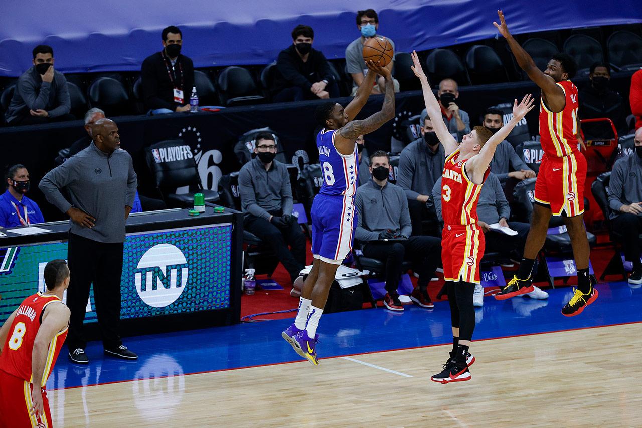 Shake Milton shooting a three pointer over three Atlanta Hawks players