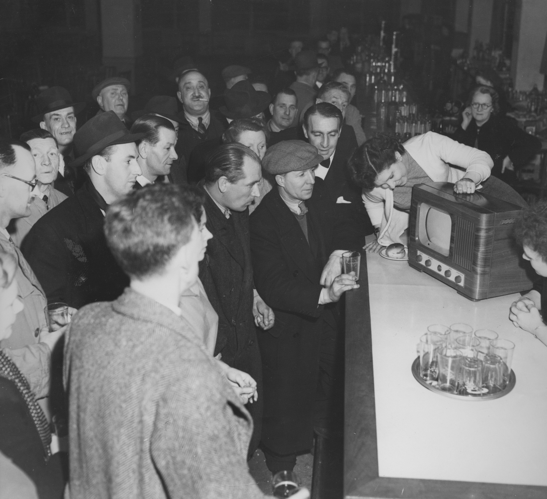 Boxing fans watch a televised fight between Albert Finch of Britain and Baby Day (Lewis Warren) of the USA, in a bar, UK, 7th February 1950. Day won on points.