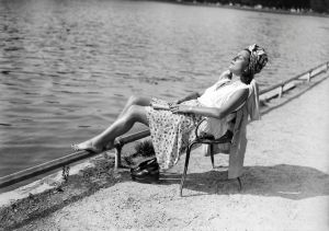 A woman rests and tans near a lake in the Bois de Boulogne near Paris, in June 1946, during a heat wave at the beginning of the 1946 summer.
