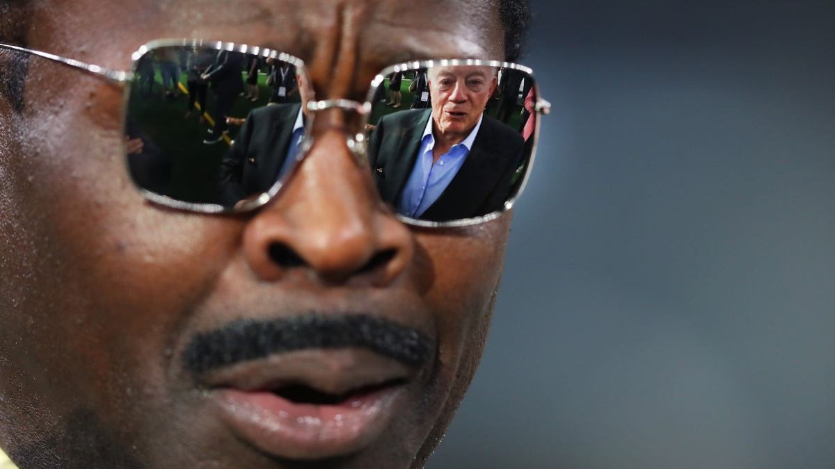 A photograph of Michael Irvin with the hideous image of Jerry Jones reflected in his sunglass lenses.