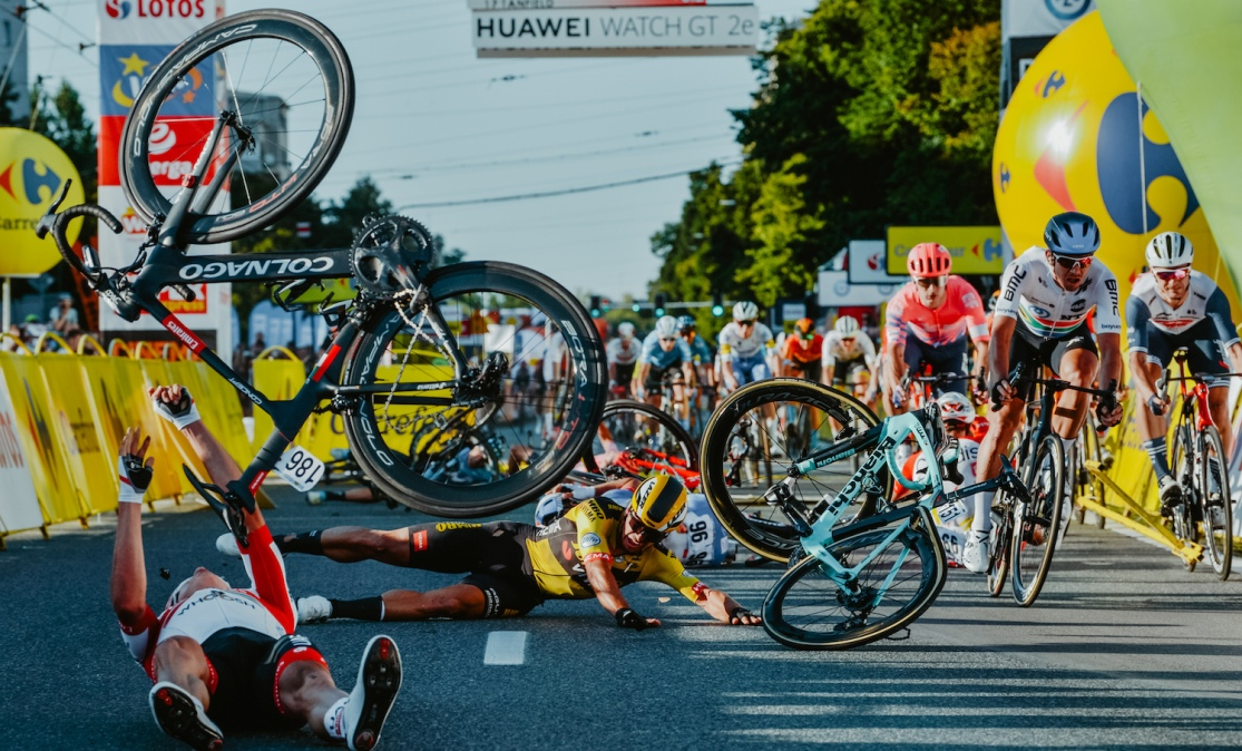 TOPSHOT - Dutch cyclist Dylan Groenewegen (on the ground ,C) and fellow riders collide during the opening stage of the Tour of Poland race in Katowice , southern Poland on August 5, 2020. - Dutch rider Fabio Jakobsen was fighting for his life on Wednesday after he was thrown into and over a barrier at 80km/h in a sickening conclusion to the opening stage of the Tour of Poland. (Photo by Szymon Gruchalski / Forum / AFP) (Photo by SZYMON GRUCHALSKI/Forum/AFP via Getty Images)