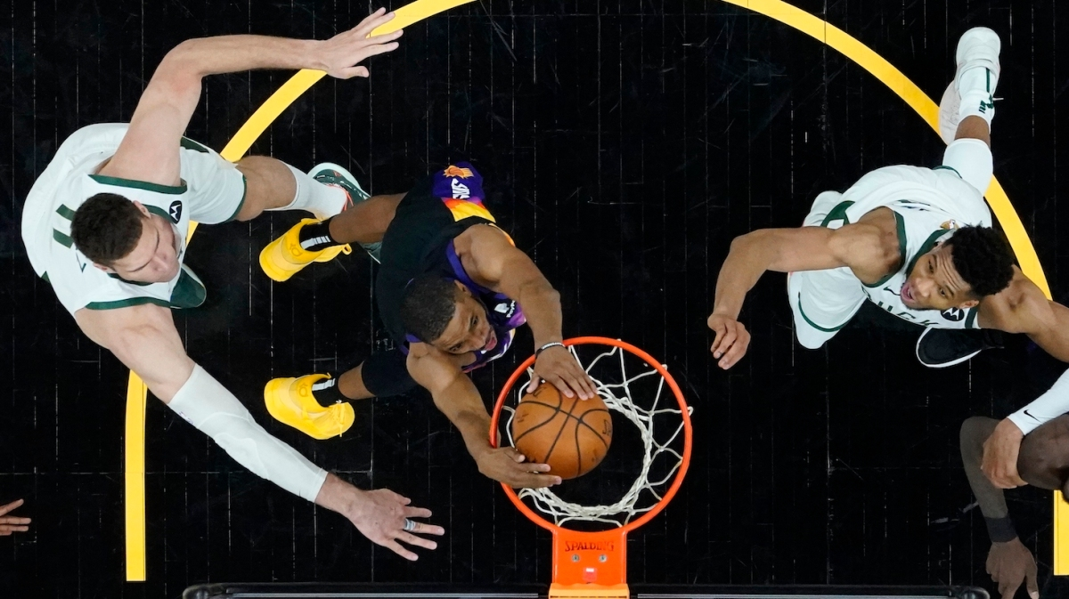 PHOENIX, ARIZONA - JULY 08: Phoenix Suns forward Mikal Bridges, middle, dunks against Milwaukee Bucks center Brook Lopez, left, and Bucks forward Giannis Antetokounmpo, right, during the second half of Game Two of the NBA Finals at Phoenix Suns Arena on July 08, 2021 in Phoenix, Arizona. NOTE TO USER: User expressly acknowledges and agrees that, by downloading and or using this photograph, User is consenting to the terms and conditions of the Getty Images License Agreement. (Photo by Ross D. Franklin-Pool/Getty Images )