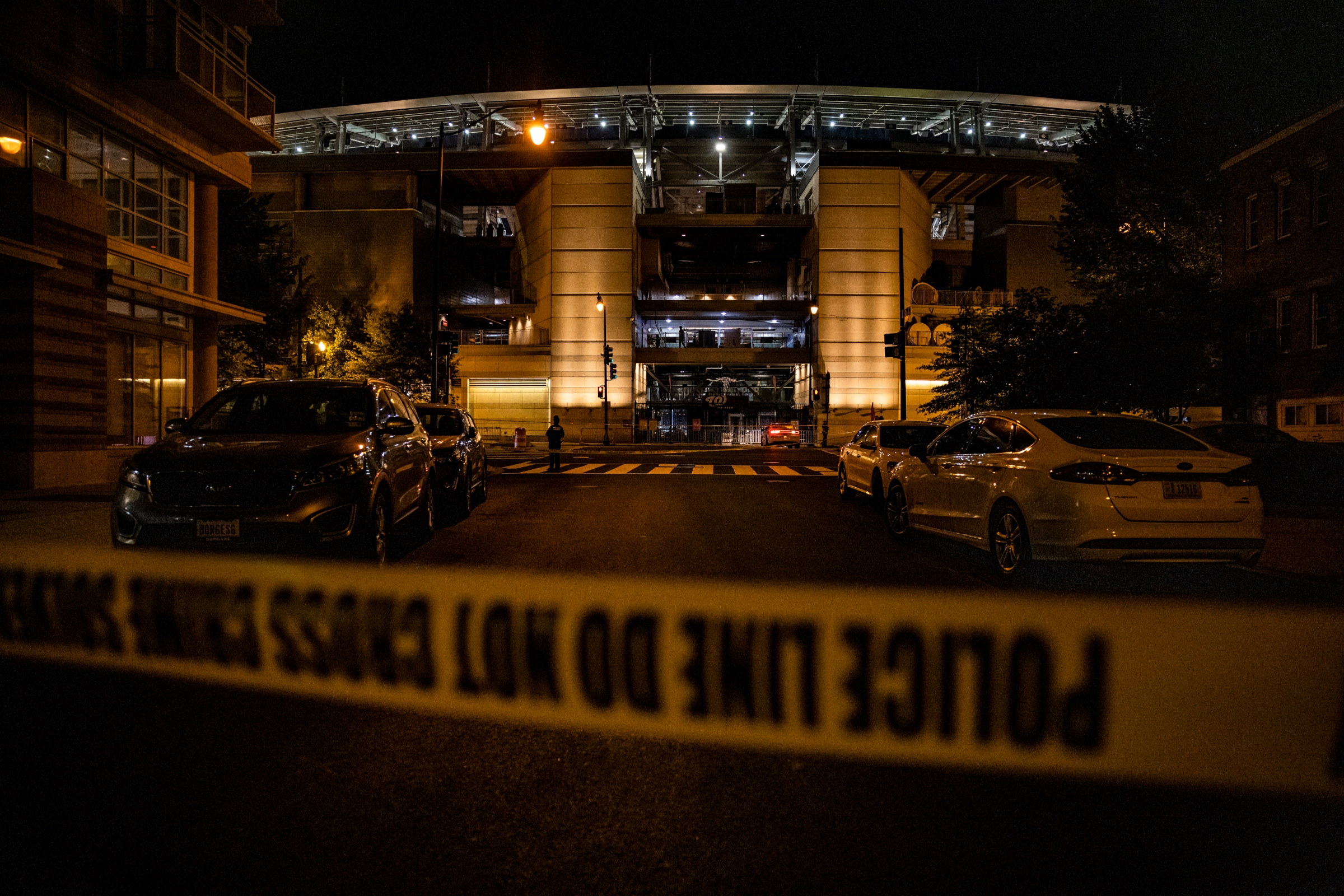 A photo of police tape and police cars in front of Nationals Park