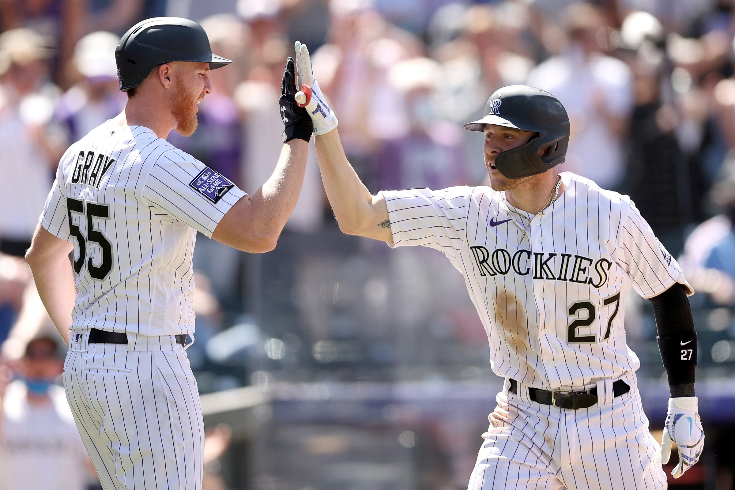 Rockies pitcher Jon Gray and Rockies shortstop Trevor Story high-five in a game against the Phillies