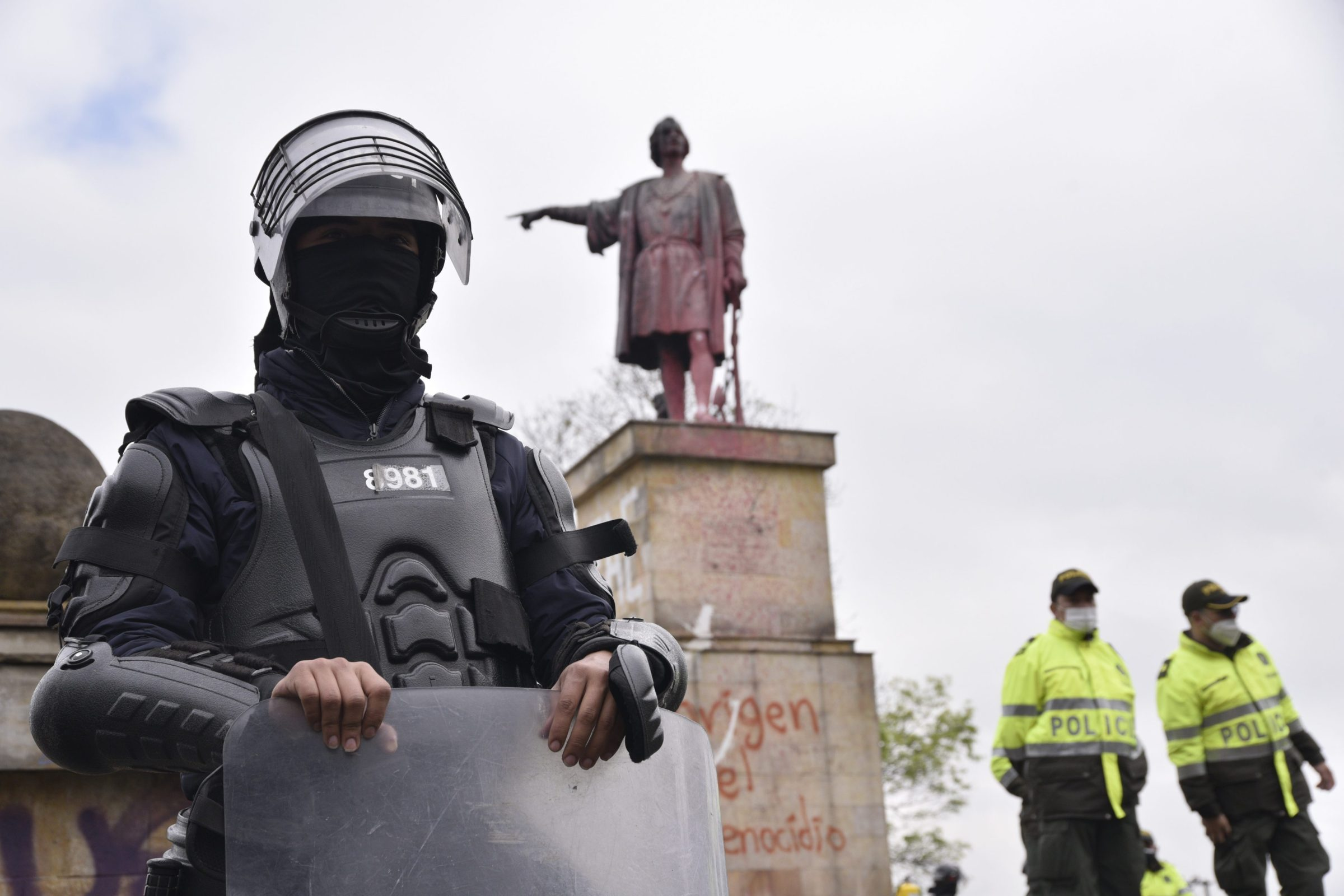 A statue of Christopher Columbus in Bogota, Colombia, defaced by protestors, is protected by armed police.
